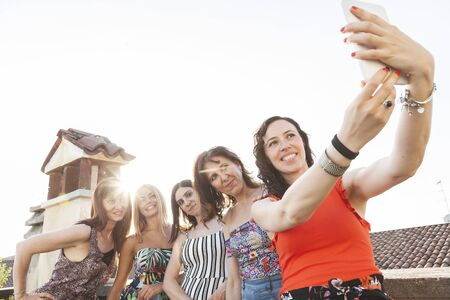 group of female friends taking a selfie with smarthphone - people having fun on the trend of new technology - Concept of friendship with girls sharing the moment on social media networks