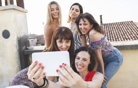 group of female friends taking a selfie with smarthphone - people having fun on the trend of new technology - Concept of friendship with girls sharing the moment on social media networks Foto de archivo