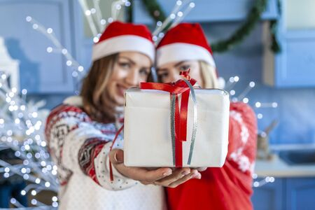 portrait of two young sisters embraced they showing a gift in christmas day Stok Fotoğraf