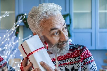 grandpa with white beard happy while receiving a Christmas gift at home Imagens