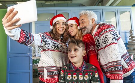 happy family reunited on Christmas day taking a selfie around the table at home Stok Fotoğraf