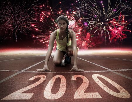 2020 New Year celebration on the racing lane with young female athlete at starting block under fireworks. New Year arrival concept