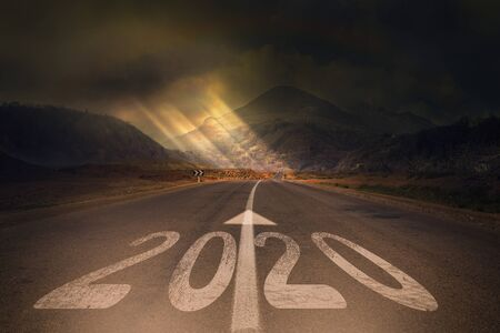 2020 New Year celebration on the asphalt road with the sunbeam coming out of the clouds. New Year arrival concept