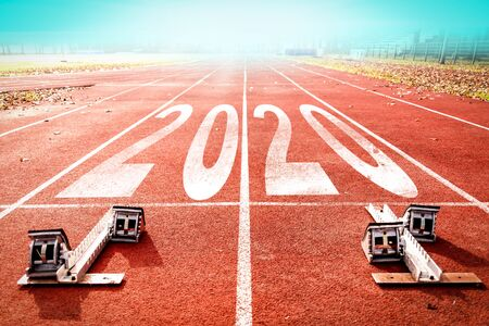 2020 New Year celebration on the racing lane with starting block. New Year arrival concept Imagens