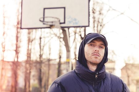 portrait of young rapper posing in the middle of an outdoor basketball court on the outskirts