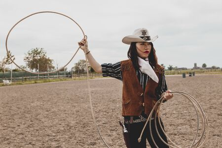 pretty Chinese cowgirl throwing the lasso in a horse paddock on a wild west farm Reklamní fotografie