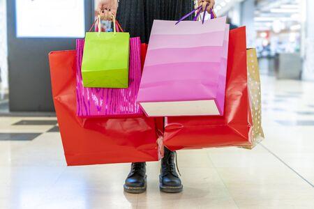 la donna sta mostrando le borse della spesa colorate al centro commerciale durante le vacanze Archivio Fotografico