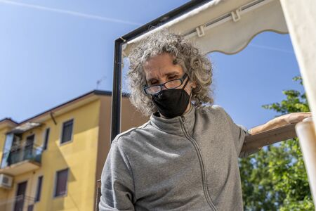 expert craftsman is repairing a balcony awning at the end of the coronavirus lockdown