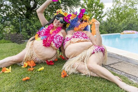 two female friends in Hawaiian costumes have fun sitting on a lawn in front of the swimming pool