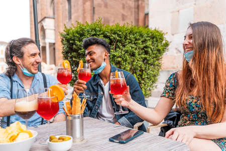 Friends drinking colored cocktail at outdoor bar with face masks - New normal lifestyles concept with happy people toasting drinks outside 免版税图像