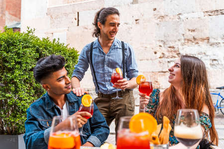 Friends drinking colored cocktail at outdoor bar - New normal lifestyles concept with happy people toasting drinks outside