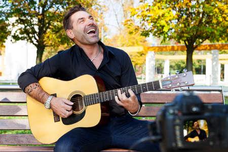 young man guitar teacher making a videos about practical guitar exercises in a public park Standard-Bild