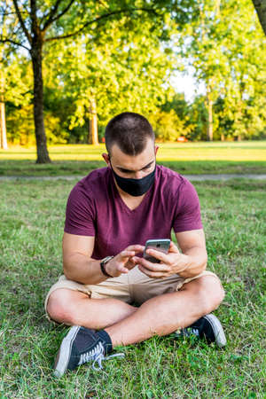 young handsome man using smart phone outdoors wearing an anti contagion face mask during the covid-19 emergency Archivio Fotografico