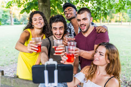 multiethnic group of millennial friends take a selfie while celebrating a birthday outdoors Stock Photo