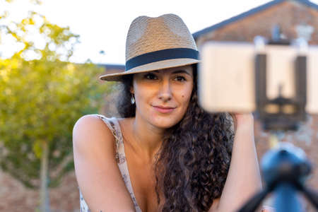 cute young woman getting ready to talk and record a video in front of the smartphone