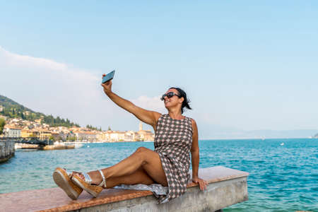 pretty woman take a selfie on vacation on the lake in summer