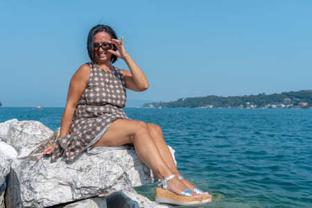 pretty woman on vacation is tanning sitting on a rock on the lake in summer