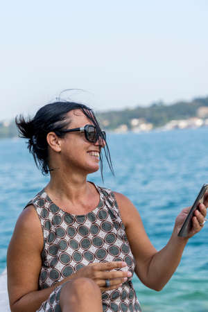pretty woman on vacation uses smartphone to share content on social networks