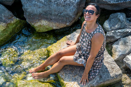 adult woman refreshes her feet in the fresh lake water sitting on a rock in summer