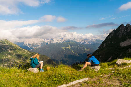 two female tourist friends are taking a break in the high mountains during a hike in the dolomites