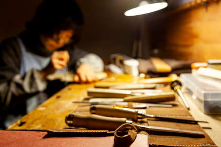 female artisan violinmaker while viewing a new violin in the laboratory Archivio Fotografico