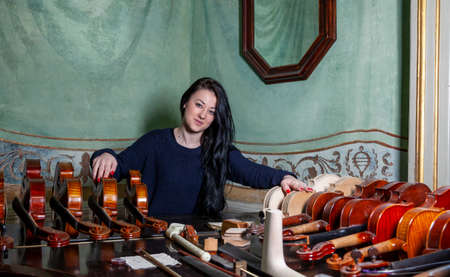 Fascinating violinist showing his collection of handcrafted violins at home Reklamní fotografie