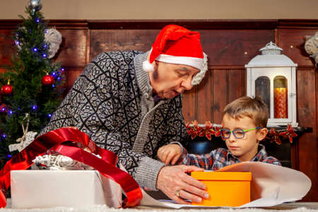 happy grandfather is teaching his grandson how to wrap christmas gifts on the table