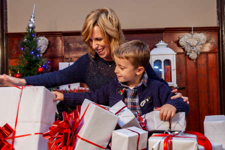 happy mom and son are opening gifts on christmas night at home