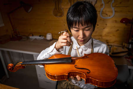 young Chinese violin maker at work in her workshop