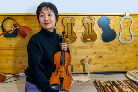 young Chinese violin maker at work in her workshop Stock Photo