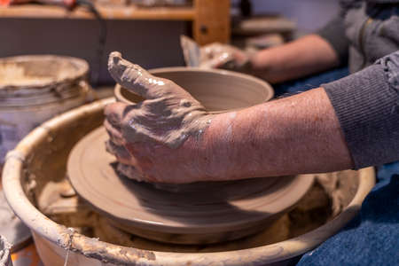 close-up on male hands working on a potters wheel to make a bowl