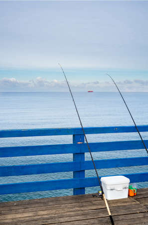 Two fishing rods leaning against the wooden rail of a pier on the Baltic Sea. Fishing at sea.