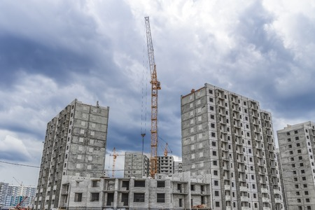 Hoisting cranes and construction of high-rise buildings Stock Photo