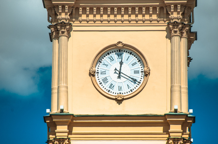 Yellow clock tower against the blue sky. Stock Photo