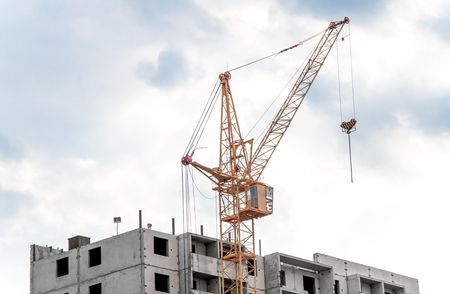 Crane and building construction against blue sky. Stock Photo
