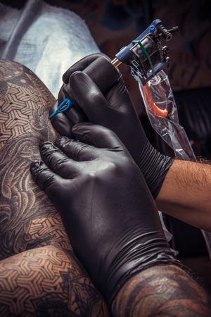 Man wearing gloves working tattooing in salon. Tattooer makes cool tattoo in tattoo studio.