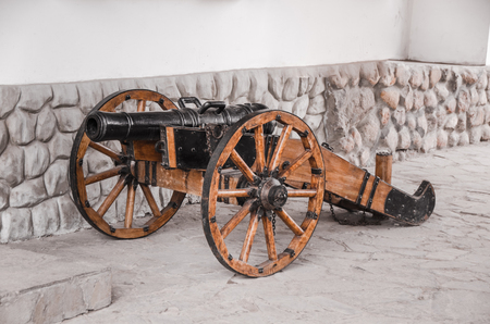 Old gun on wheels about a fortification. Stock Photo