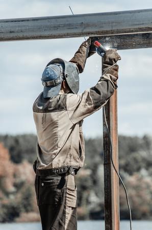 voltaic: Welder worker in protective mask welding metal by electrode.