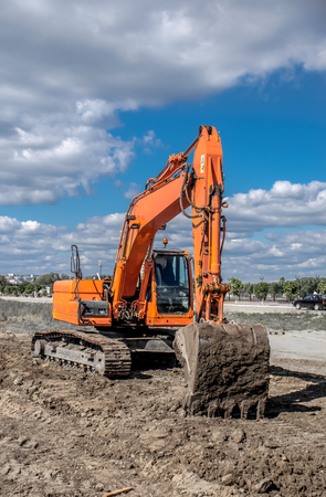 Orange excavator on a sunny day with the blue sky in the background. Stock Photo