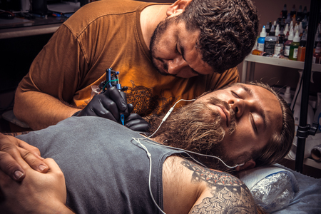 Professional tattoo artist create tattoo in studio. Tattooist at work in tattoo parlor.
