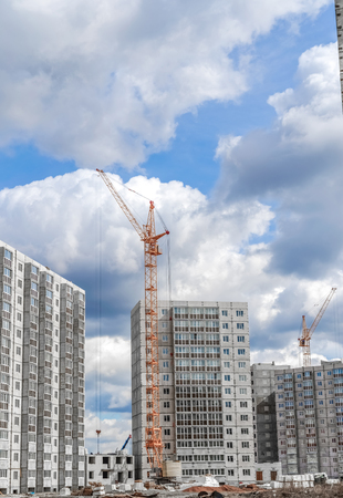 Industrial cranes and new highrise building Stock Photo