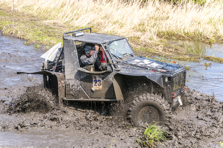 SALOVKA, RUSSIA - MAY 5, 2017: Unidentified racer at off-road car passes through muddy puddles in the Trofi rubezh 2017