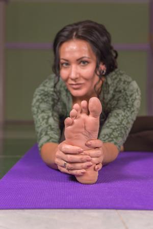 Professioneller Yogatrainer, der Yoga asana in der Turnhalle zeigt