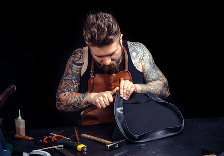 Artisan at work on his new leather product in his workplace Banco de Imagens