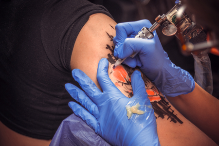 Master tattooist working on professional tattoo machine device in tattoo studio Zdjęcie Seryjne - 93621320