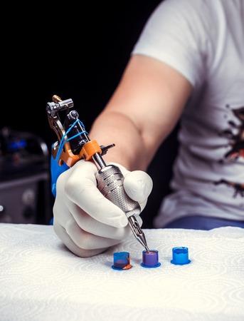 タトゥーガンを持ったタトゥーイストの手。