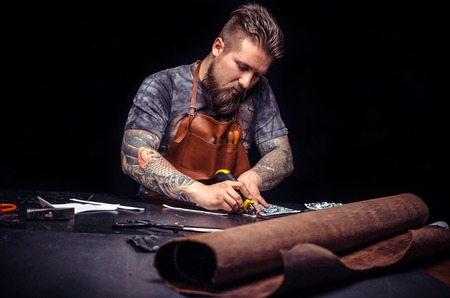 Artist working with leather keen on ones business Stock Photo