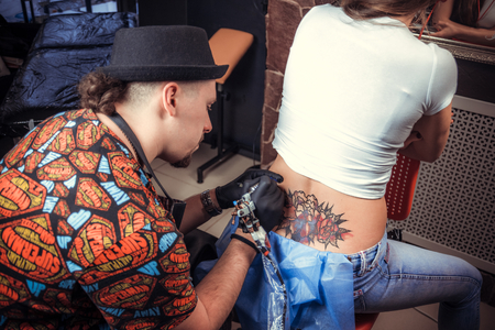 Skin master demonstrates process of making a tattoo Imagens