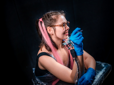 Tattoo artist poses in a tattoo studio