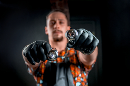 Tattooer with a tattoo-machine in tattoo studio